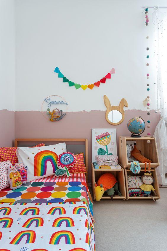 une chambre d'enfant colorée avec un mur de blocs de couleur, une literie et des jouets colorés, des guirlandes lumineuses et un miroir de lapin