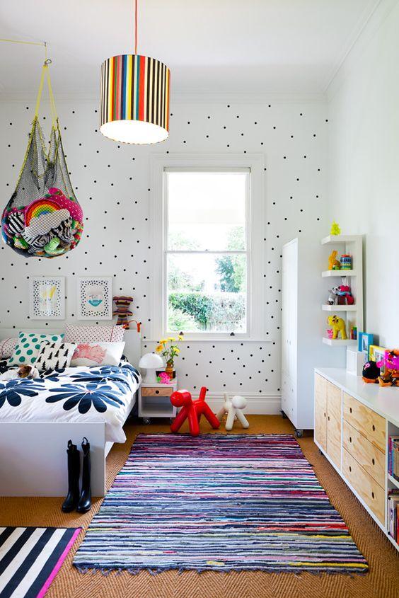 une chambre d'enfant colorée avec un mur à pois, une literie et des tapis colorés, des jouets audacieux dans des filets au-dessus du lit