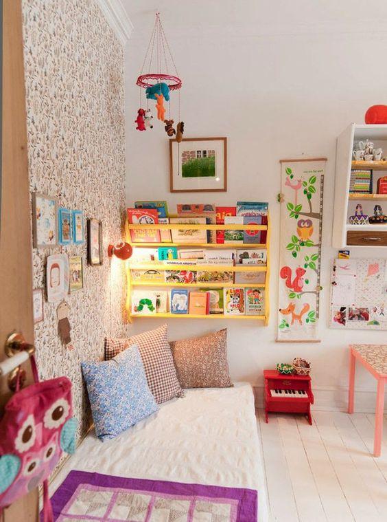 une chambre d'enfant colorée avec un mur de papier peint, une étagère jaune, des œuvres d'art lumineuses et de la literie et des jouets colorés