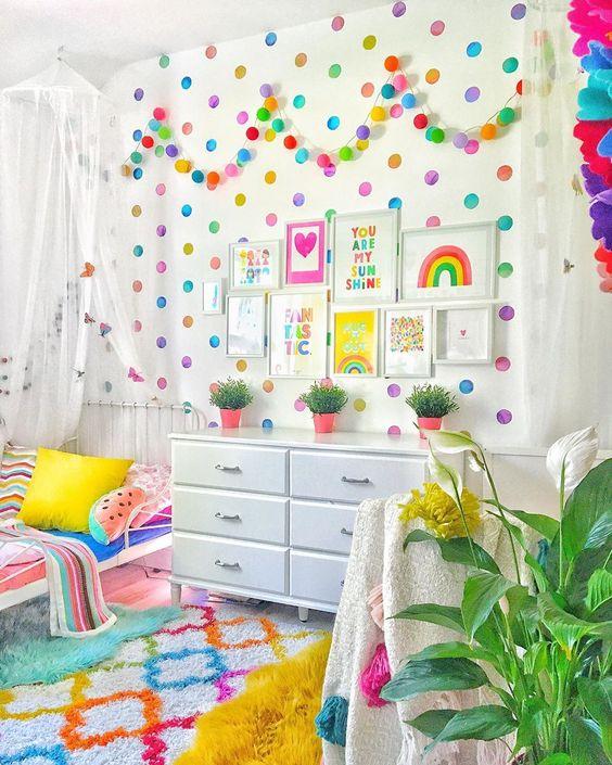 un espace enfant coloré avec un mur à pois, une guirlande audacieuse, une literie lumineuse et des oreillers de fruits et un tapis audacieux épatant
