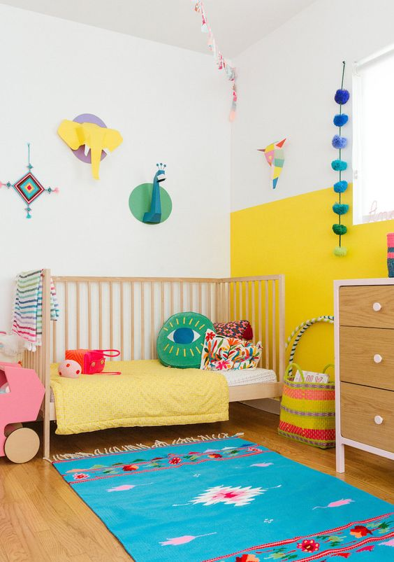 une chambre d'enfant moderne et colorée avec un mur de blocs de couleur jaune et blanc, une literie lumineuse et un tapis, une taxidermie en carton et des accessoires