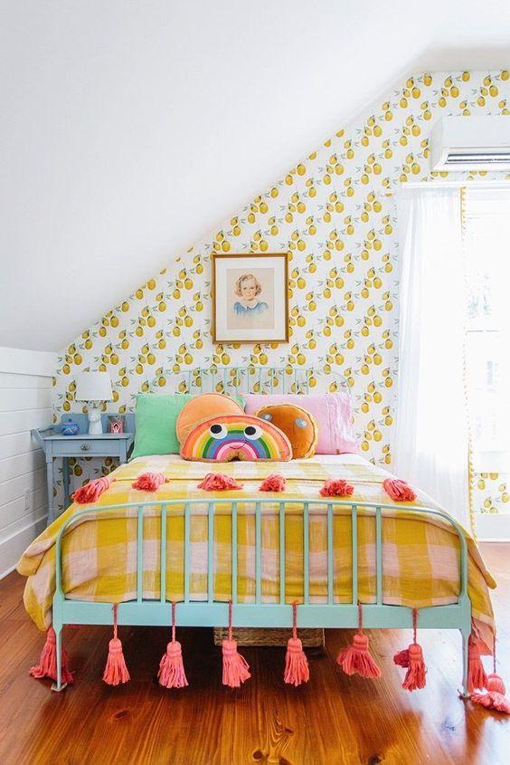 une chambre d'enfant colorée avec un papier peint à imprimé fruits rétro, une literie colorée, des œuvres d'art, des pompons et une table de chevet bleue