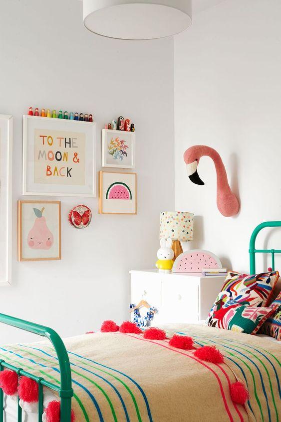 une chambre d'enfant pastel avec des œuvres d'art pastel, une fausse taxidermie, une literie lumineuse et un lit vert audacieux