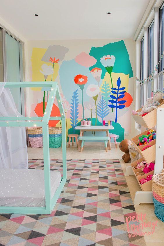 une chambre d'enfant pastel avec un mur floral lumineux, un lit en forme de maison à la menthe, des jouets colorés et un tapis et des paniers audacieux