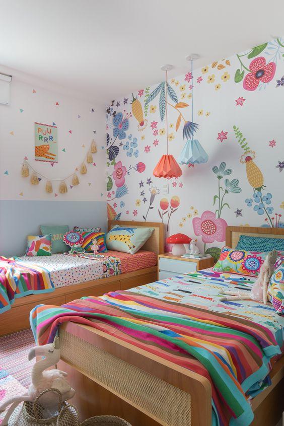 une chambre d'enfant jumelle colorée avec un mur floral, une literie et des oreillers colorés, des suspensions et une guirlande de pompons