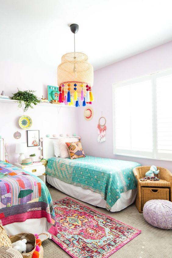 une chambre d'enfants partagée pastel avec des murs de lavande et un pouf, une literie colorée et des œuvres d'art et une lampe avec des pompons colorés