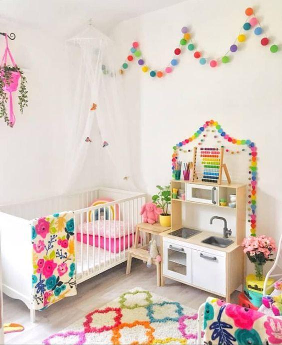 une chambre d'enfant éclaboussée d'arc-en-ciel avec des guirlandes colorées, un tapis audacieux, une literie colorée et une jardinière rose vif