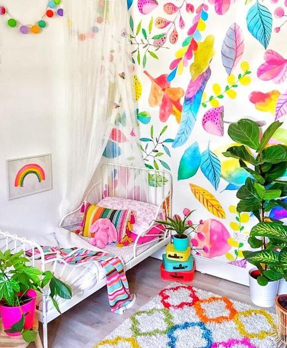 une chambre d'enfant super lumineuse avec un mur botanique coloré, une literie lumineuse et un tapis, des mini valises colorées et une jardinière rose vif