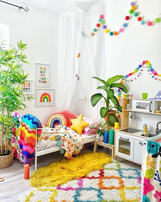 une chambre d'enfant super audacieuse avec des guirlandes de couleur arc-en-ciel, une literie, des couvertures et des oreillers assortis, un tapis coloré et des œuvres d'art