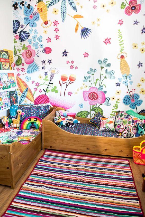 une chambre d'enfant colorée partagée avec un mur floral lumineux et une literie audacieuse, un tapis à rayures audacieuses et des livres sur les étagères