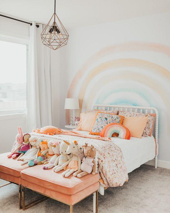 une chambre d'enfant arc-en-ciel pastel avec un arc-en-ciel au mur, une literie colorée et des tabourets pêche avec des jouets