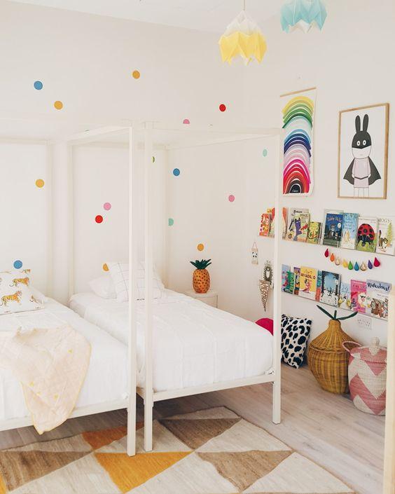 une chambre d'enfant partagée faite dans des tons neutres mais rehaussée de couleurs vives - pois sur le mur, art coloré, guirlandes et livres