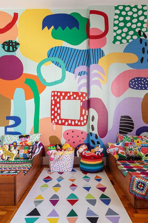 une chambre d'enfant partagée super colorée avec un mur abstrait audacieux, des draps et des paniers colorés, des jouets audacieux