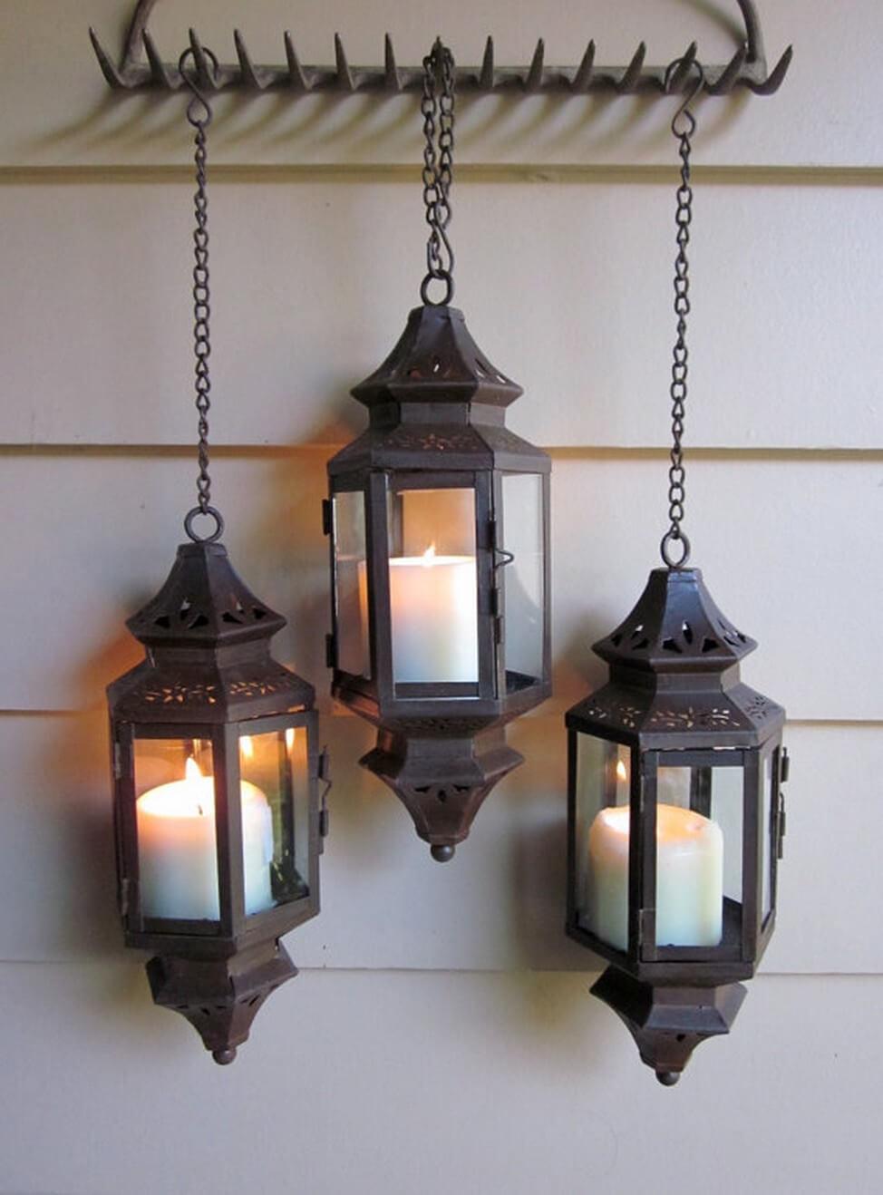 Trois lanternes percées sur un cintre de râteau
