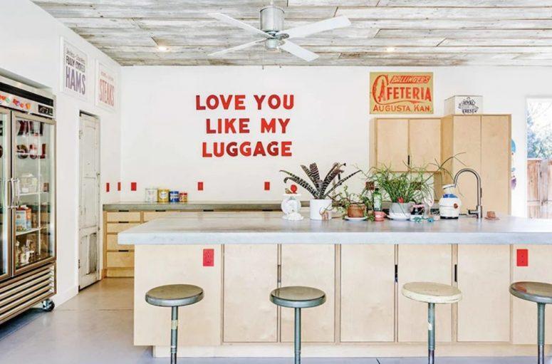 La cuisine est un espace confortable avec des touches rétro, des meubles en contreplaqué et même un réfrigérateur aux allures de magasin