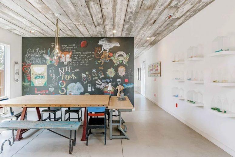 La salle à manger comprend un mur d'art audacieux et des chaises et des bancs dépareillés pour une sensation shabby chic