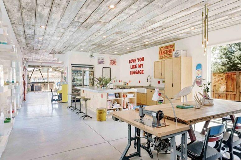 La disposition principale est un espace cuisine-salle à manger avec une zone d'artisanat, des ampoules suspendues et un décor cool