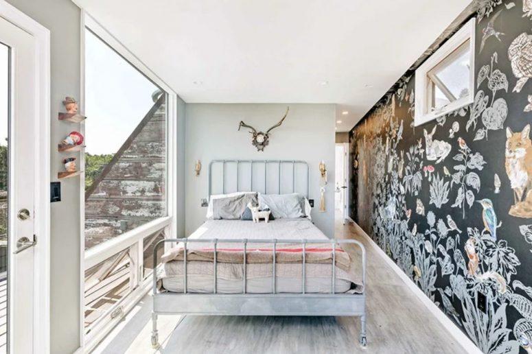 La chambre des enfants est faite avec un mur noir avec beaucoup d'art dessus et un mur vitré avec une entrée sur le balcon