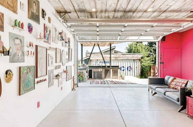 Ce salon est très audacieux avec sa moitié fait en rose, un mur de galerie audacieux et un accès à la cuisine extérieure