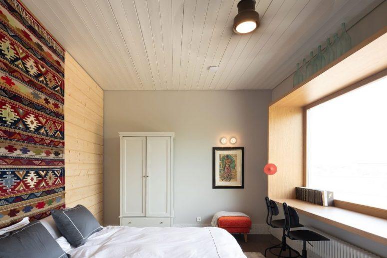 La chambre principale est faite avec des textiles clairs et un tabouret orange plus une grande fenêtre avec un bureau de fenêtre