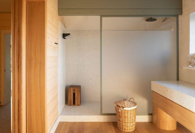La salle de bain est faite de carreaux de pierre neutres et de bois clair