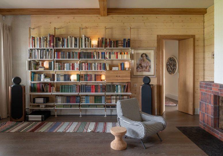 Il y a une grande étagère ouverte, une chaise à carreaux et une cheminée pour un coin lecture confortable