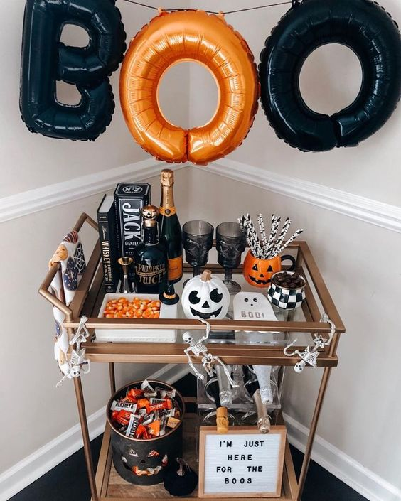 un chariot de bar d'Halloween audacieux avec une guirlande de lettres orange et noire, des citrouilles, des bonbons, une œuvre d'art et des squelettes