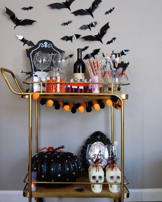 un chariot de bar d'Halloween audacieux avec une guirlande de pompons brillants, une citrouille à pointes noires, des crânes, des chauves-souris sur le mur
