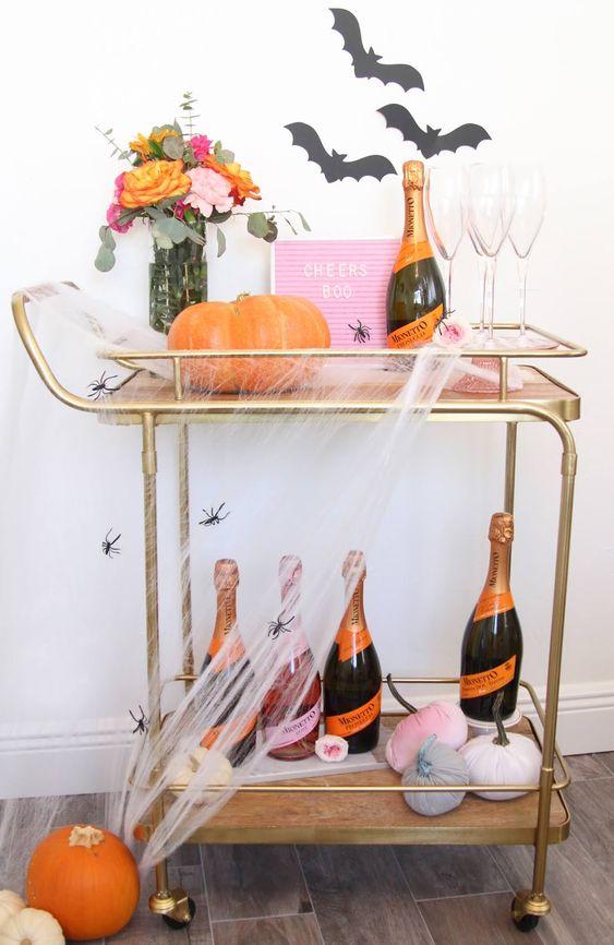 un chariot de bar Halloween lumineux avec un panneau rose, des citrouilles en velours, des chauves-souris sur le mur, des fleurs lumineuses, des toiles d'araignées et des araignées