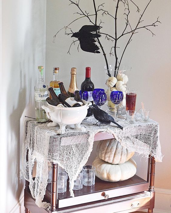un chariot de bar Halloween coloré avec une étamine, des citrouilles neutres, des verres bleus, un vase de citrouille avec des branches et un corbeau