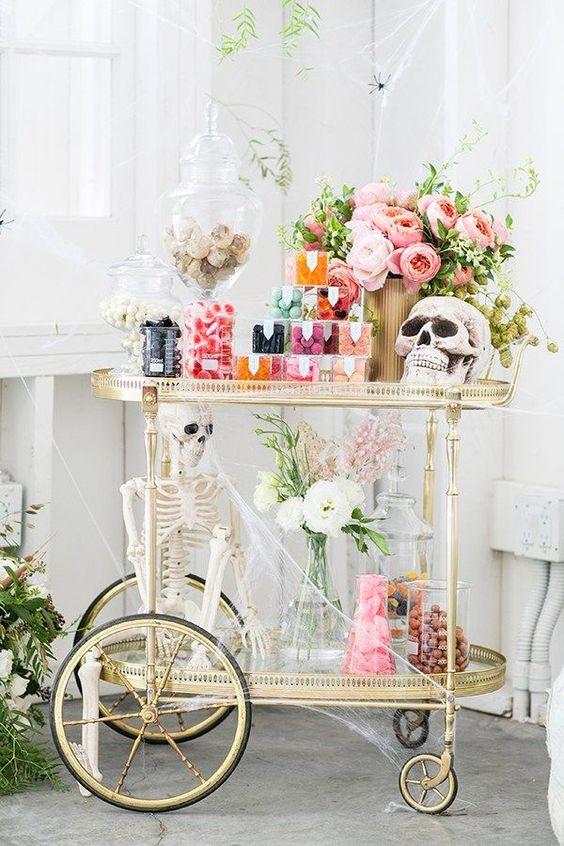 un joli bar glamour d'Halloween avec des fleurs pastel, des crânes, un squelette, beaucoup de bonbons et des bonbons avec beaucoup de toile d'araignée
