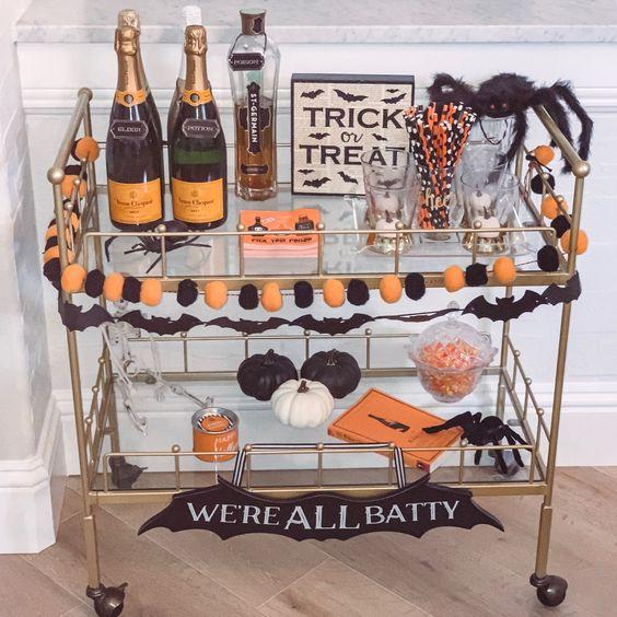 un chariot de bar d'Halloween audacieux avec une guirlande de pompons orange et noir, des citrouilles noires et blanches, des araignées noires et des boissons