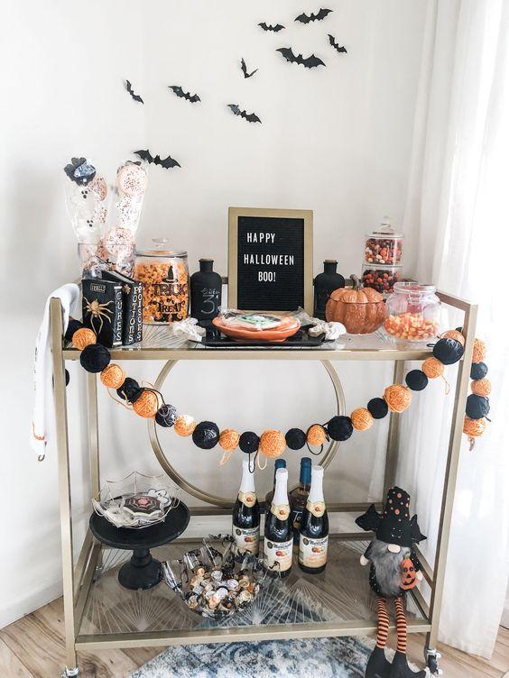un chariot de bar Halloween lumineux avec une guirlande orange et noire, un signe, des chauves-souris sur le mur, des citrouilles, des bonbons et un gnome