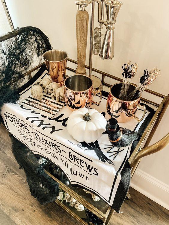 un chariot de bar d'Halloween cool avec des tasses en cuivre, un corbeau, des citrouilles blanches, des crânes, des toiles d'araignées noires et des touches brillantes