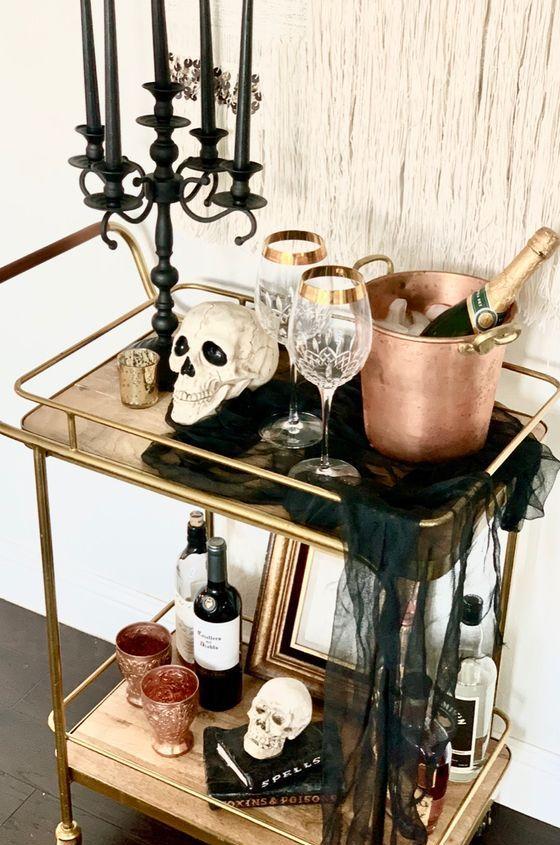 un chariot de bar d'Halloween avec des crânes, un candélabre noir avec des bougies noires, une étamine noire, de la vaisselle en cuivre et des verres élégants