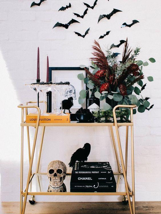 un chariot de bar d'Halloween avec un crâne embelli, un arrangement floral sombre, des bougies bordeaux et des chauves-souris sur le chariot
