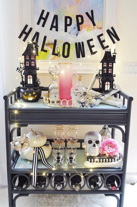 un chariot de bar glam Halloween avec des maisons effrayantes, des crânes, une fleur rose, des citrouilles neutres, des lumières et une bannière de lettre noire