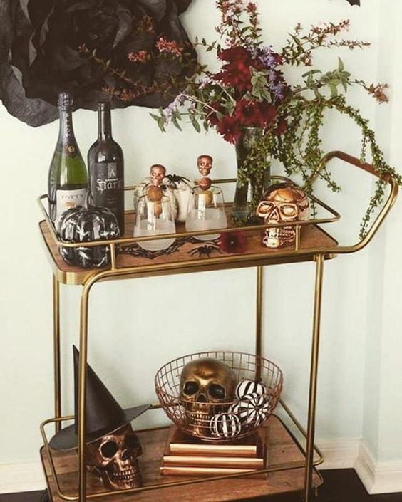 un chariot de bar glam Halloween avec une pièce maîtresse florale, des crânes dorés et en cuivre, des citrouilles et de la verdure est facile et chic