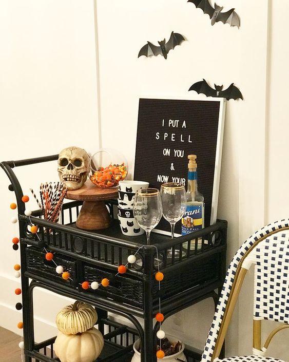 un chariot de bar d'Halloween décoré d'une guirlande à pompons, d'un crâne, d'un signe, de citrouilles et de chauves-souris dessus