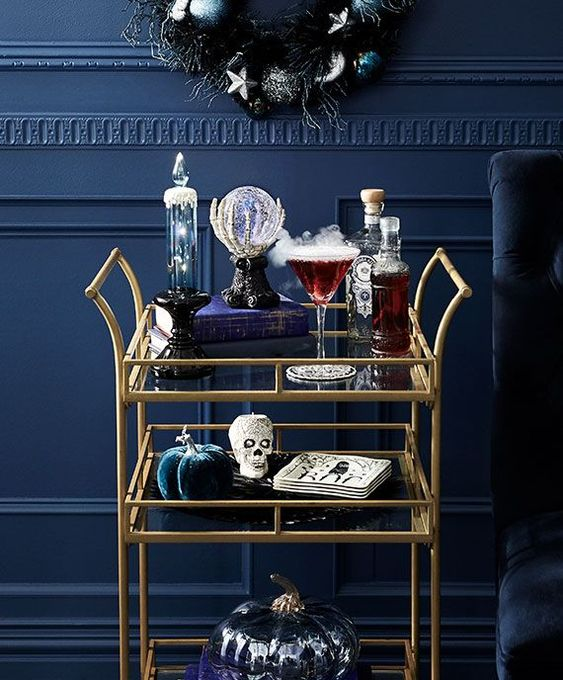 un chariot de bar d'Halloween raffiné avec des citrouilles en velours, des crânes, une boule de cristal, de la fumée et des boissons