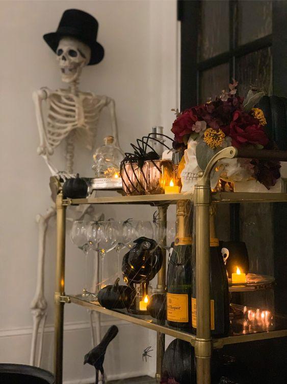 un chariot de bar d'Halloween hanté avec des bougies, des citrouilles noires, un arrangement floral sombre, des tasses en cuivre et des araignées tenues par un squelette