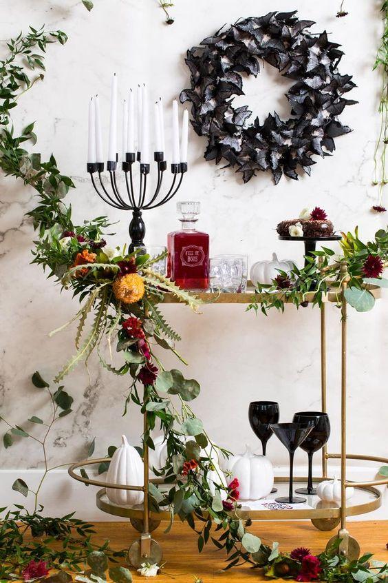 un chariot de bar d'Halloween sophistiqué avec de la verdure et des fleurs lumineuses, un candélabre avec des bougies, une couronne de papillon noire et des bonbons et des verres noirs