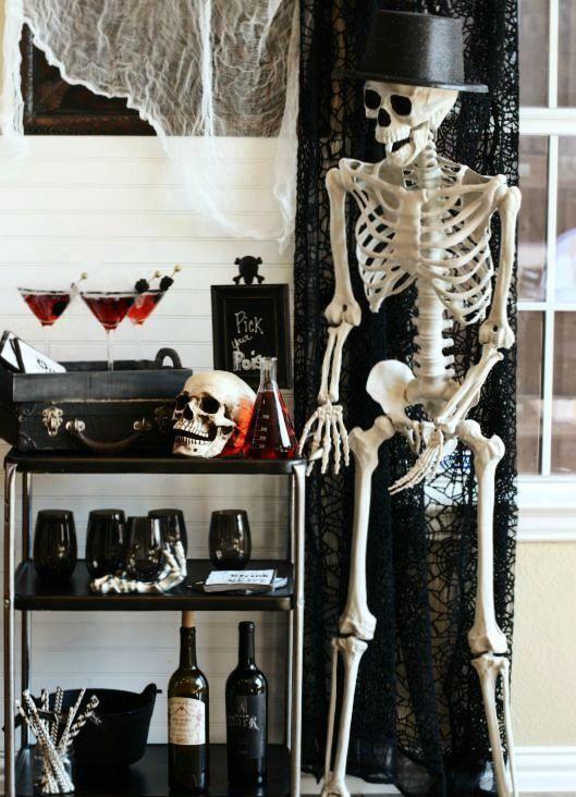 un chariot de bar Halloween effrayant avec des lunettes noires, un coffre noir avec des boissons, un crâne et des squelettes autour
