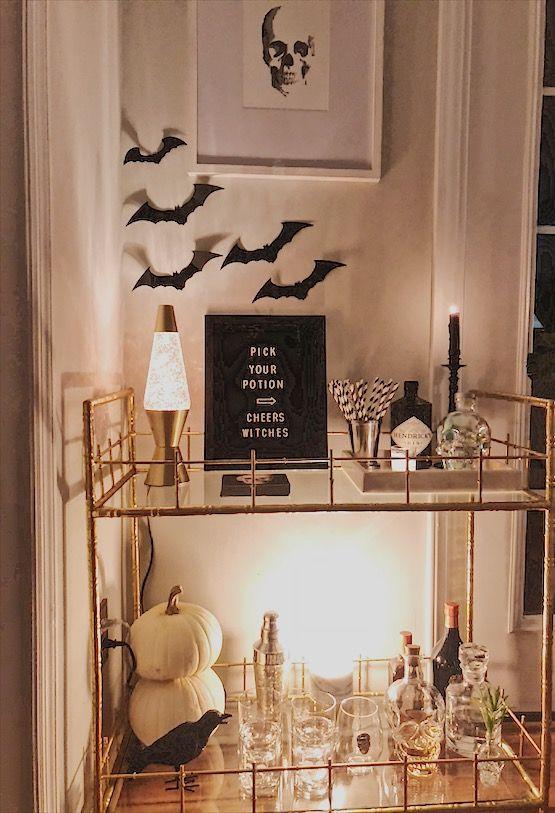 un élégant chariot de bar Halloween avec des chauves-souris sur le mur, des lampes et des bougies, des citrouilles blanches, un signe et un corbeau
