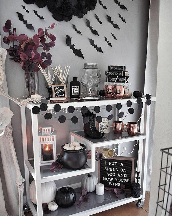 un élégant chariot de bar d'Halloween avec des citrouilles noires et blanches, des guirlandes de points noirs, des tasses en cuivre, des chauves-souris et des feuilles sombres