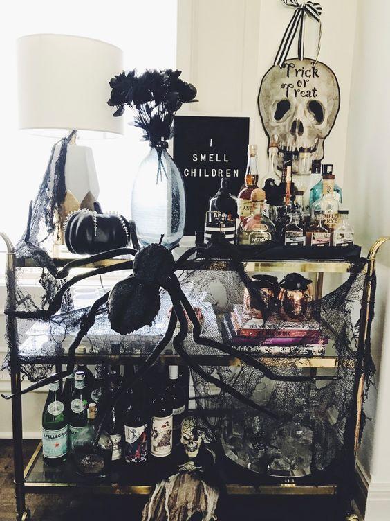 un chariot de bar d'Halloween exquis avec un panneau noir, des araignées, des citrouilles noires, une étamine noire, des fleurs sombres et beaucoup de boissons