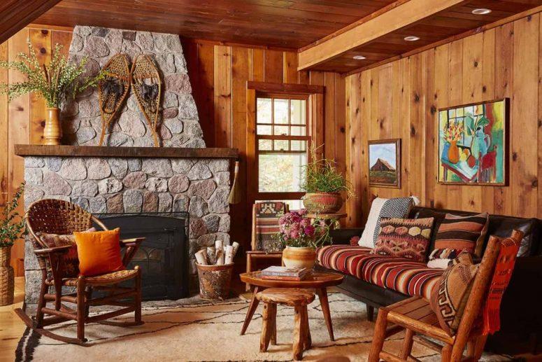 Le salon est fait de bois teinté, de meubles rustiques vintage et d'un grand foyer en pierre