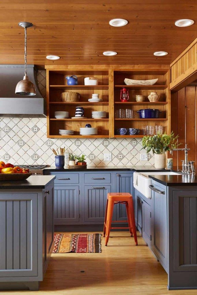 La cuisine est faite dans le bleu, avec des étagères en bois teinté au lieu des armoires supérieures et des tabourets et lampes en métal