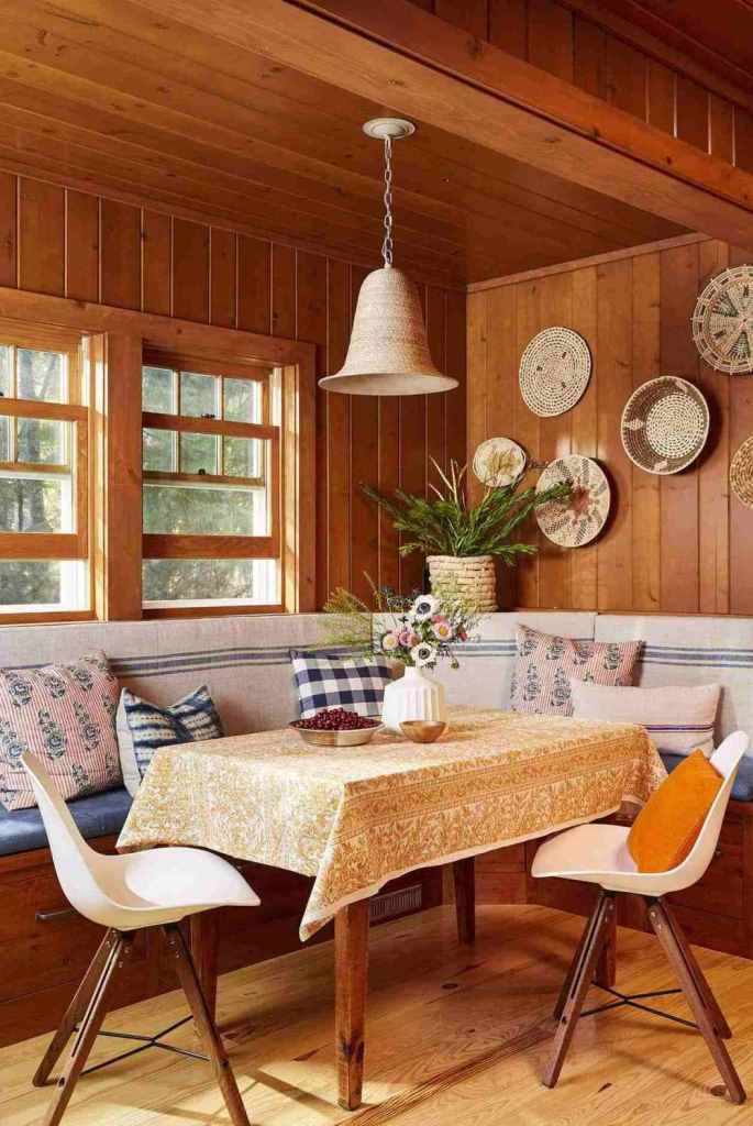 La salle à manger comprend un siège intégré avec de nombreux oreillers, des chaises et une table