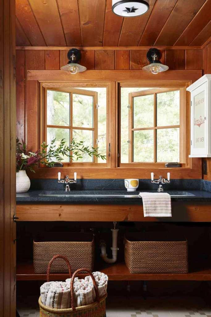 La salle de bain principale est faite avec des comptoirs en pierre, des paniers et des fleurs
